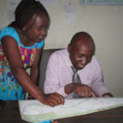 Lucy Fondo of Map Kibera assists a teacher in Kibera in finding their school on the map